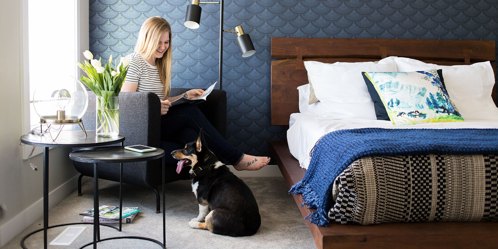 Woman reading in bedroom with dog